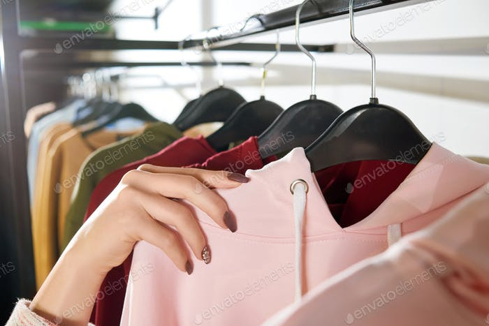 Woman's hand lying on shop hangers with clothes