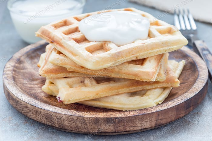 Homemade savory belgian waffles with bacon and shredded cheese on wooden plate, horizontal