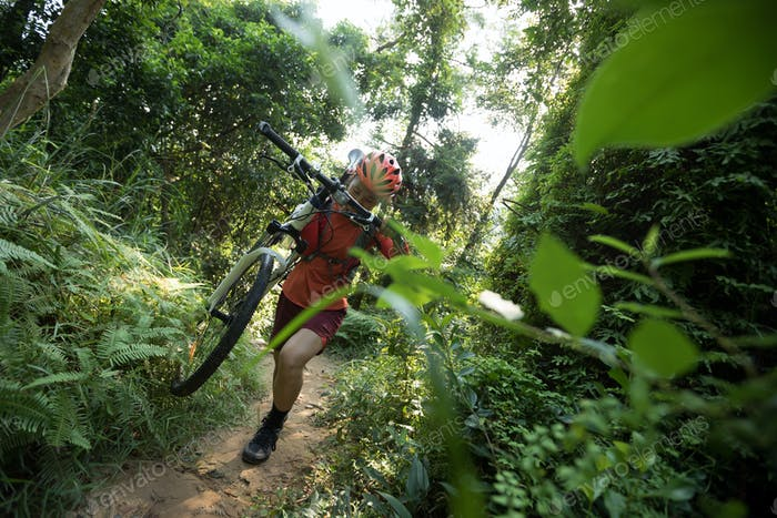 Woman mountain biker with bike climbing up the slope on forest trail