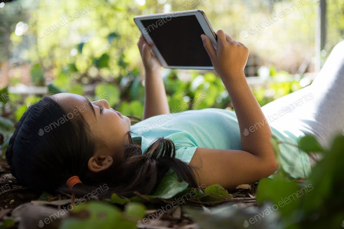 Little girl lying on ground using her tablet on a sunny day