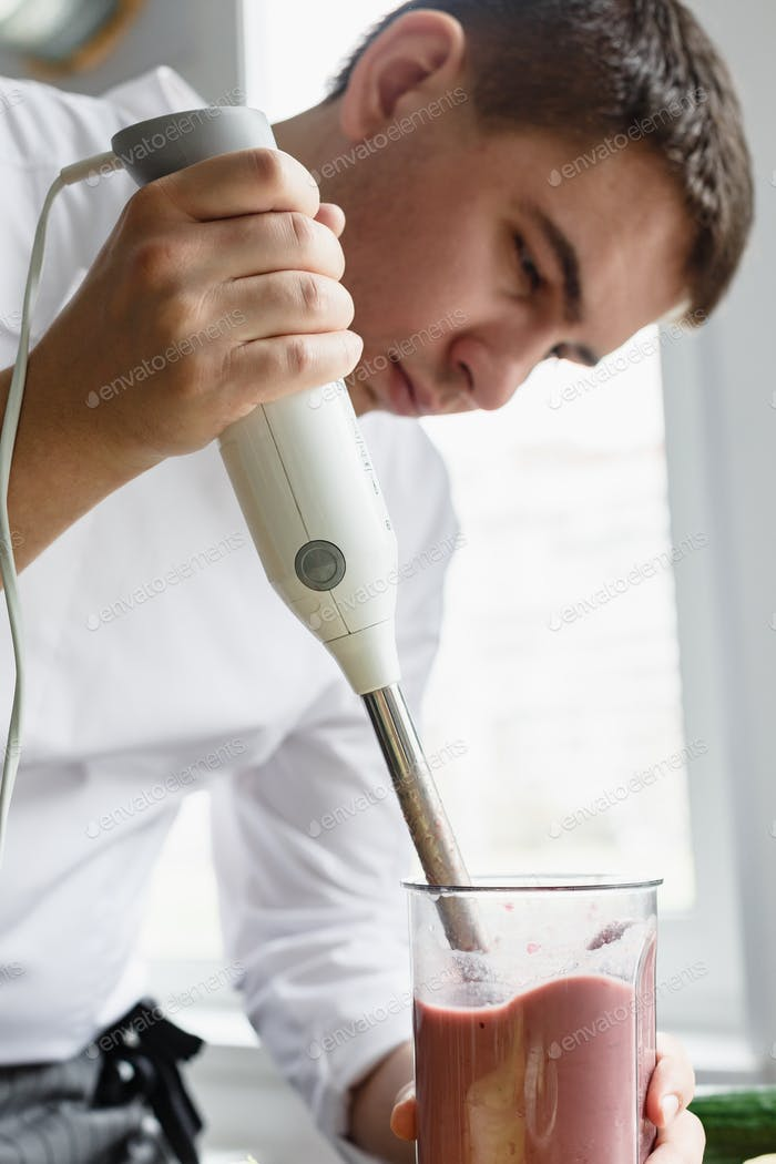 Young male preparing smoothie