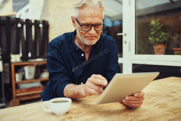 Smiling senior man using a tablet outside on his patio
