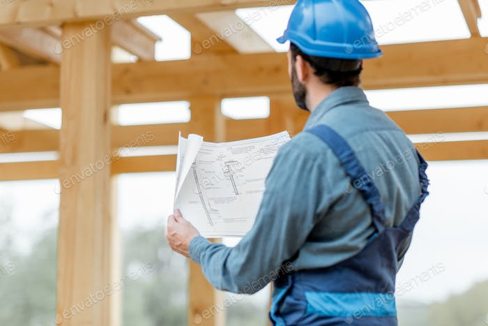 Builder with blueprints near the wooden house on the construction site