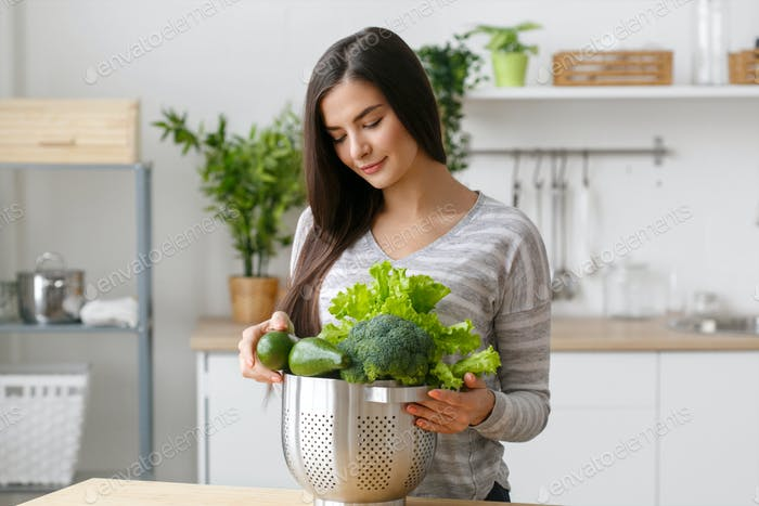Woman on kitchen home with green vegetables cooking. Helthy home food diet vitamins