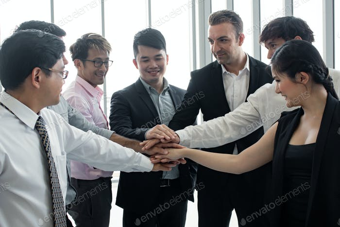 Join hands of team of Asian people and foreigners.
