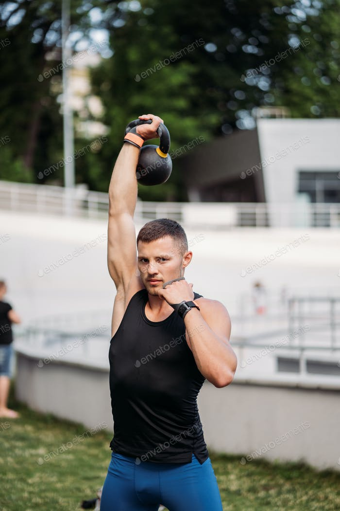 Sportive guy training with kettlebell. Strength and motivation
