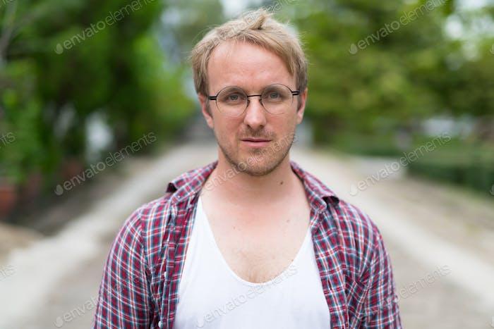 Portrait of man with blonde hair wearing eyeglasses outdoors