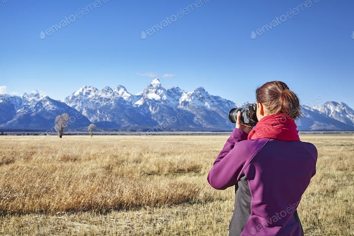 Rear view of a woman taking pictures with DSLR camera in the Gra