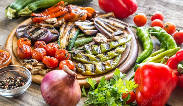 Grilled and fresh vegetables on the wooden board