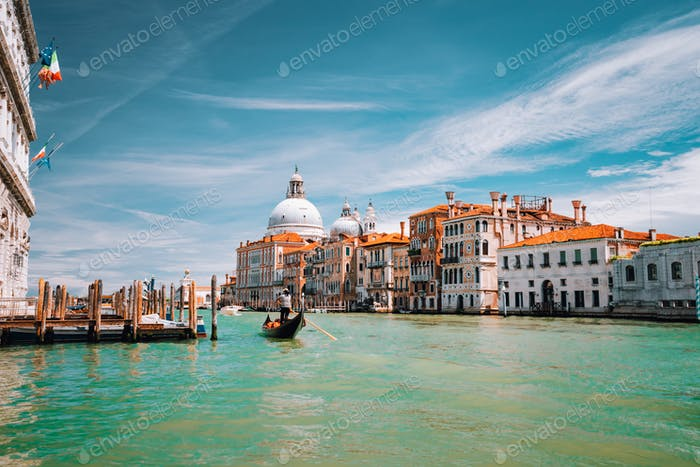 Venice, Italy. Tourist gondola trip on Grand Canal. Basilica Santa Maria della Salute against blue
