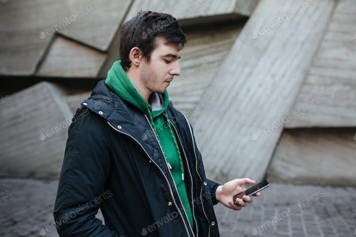 Nachdenklich Kerl in grün Sweatshirt stehen auf der Straße und suchen in seinem Handy