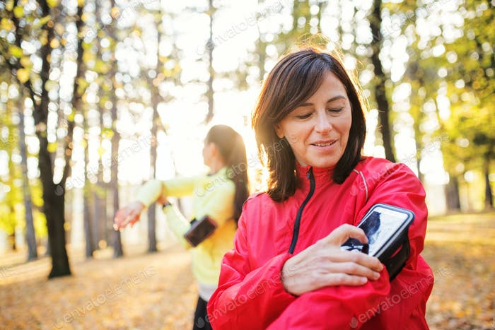Female runners with smartphone outdoors in forest in nature, measuring time.