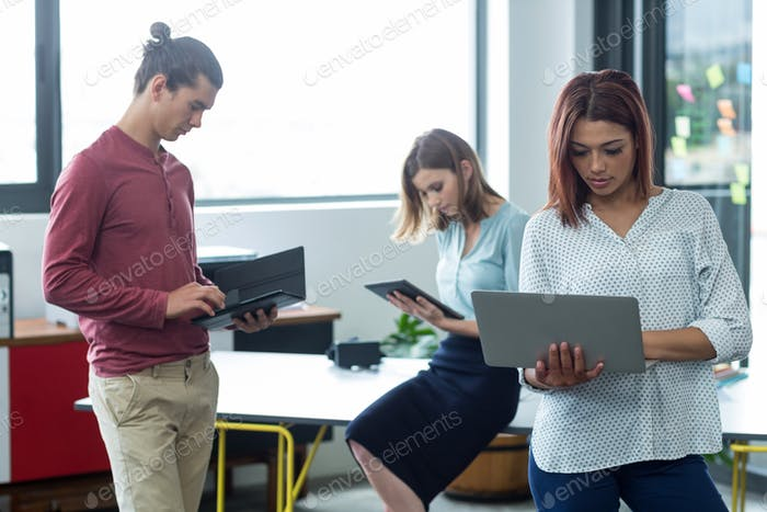 Business executive using laptop and digital tablet
