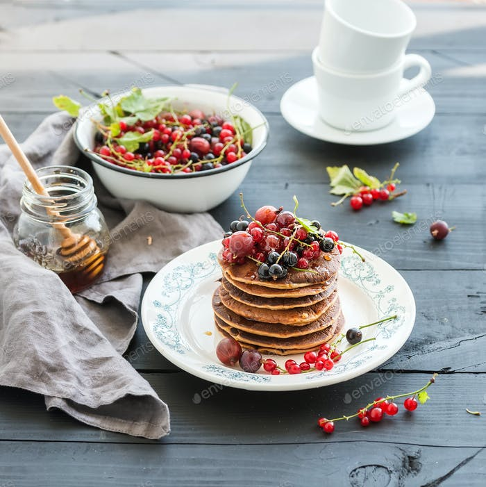 Breakfast set. Buckwheat pancakes with fresh berries and honey