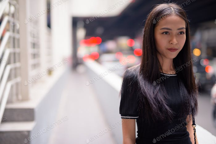 Young beautiful Asian tourist woman thinking in the city streets