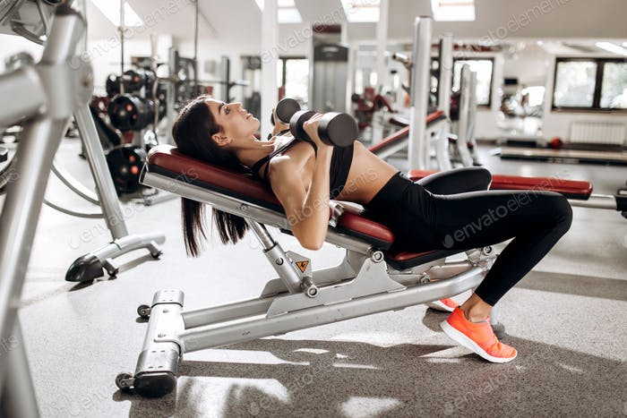 Beautiful athletic girl dressed in black sports top and tights builds up muscles with dumbbells