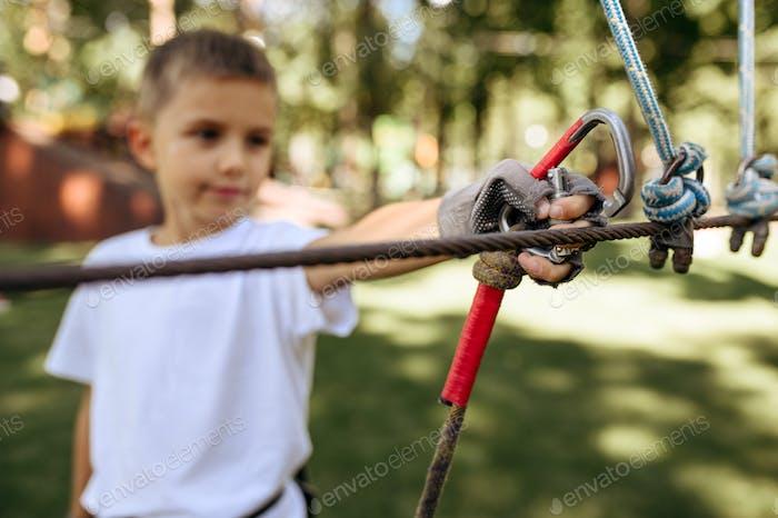 Little boy climbs in rope park, climber