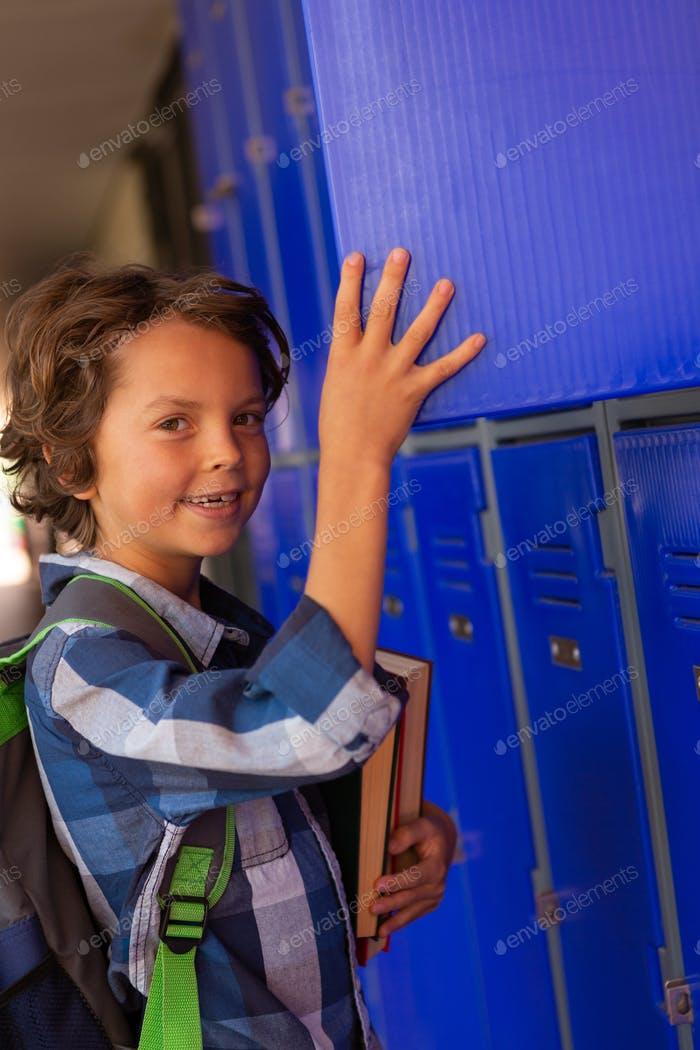 Schoolboy picking up the books out of the locker in the locker room at school