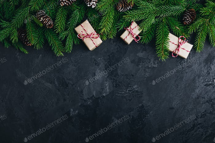 Christmas festive background with christmas tree branches, fir cones and gift boxes