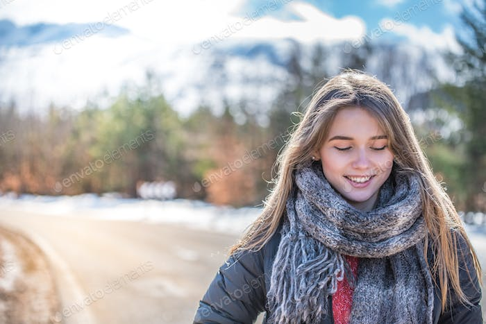 portrait Young pretty woman on a road with snow in winter