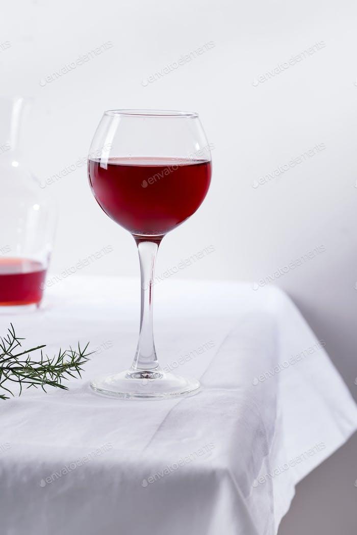 Rotwein in einem Weinglas mit Schatten auf weißem Textilhintergrund isoliert