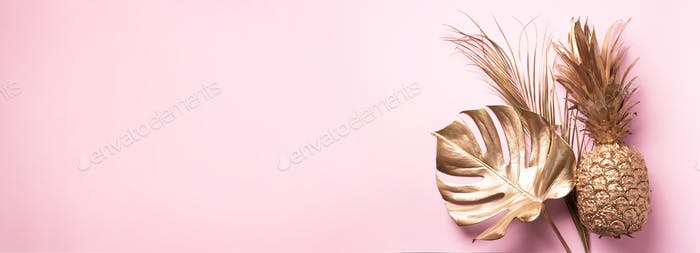 Creative layout. Gold pineapple and golden palm, monstera on pink background with copy space. Top