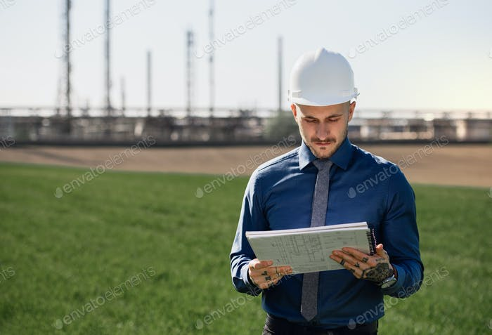 Young engineer with hard hat and tablet standing outdoors by oil refinery