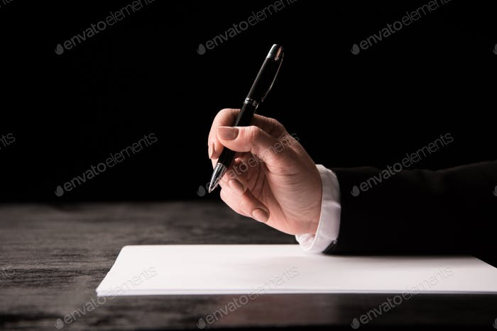 Cropped shot of a female hand holding a pen over a blank paper sheet