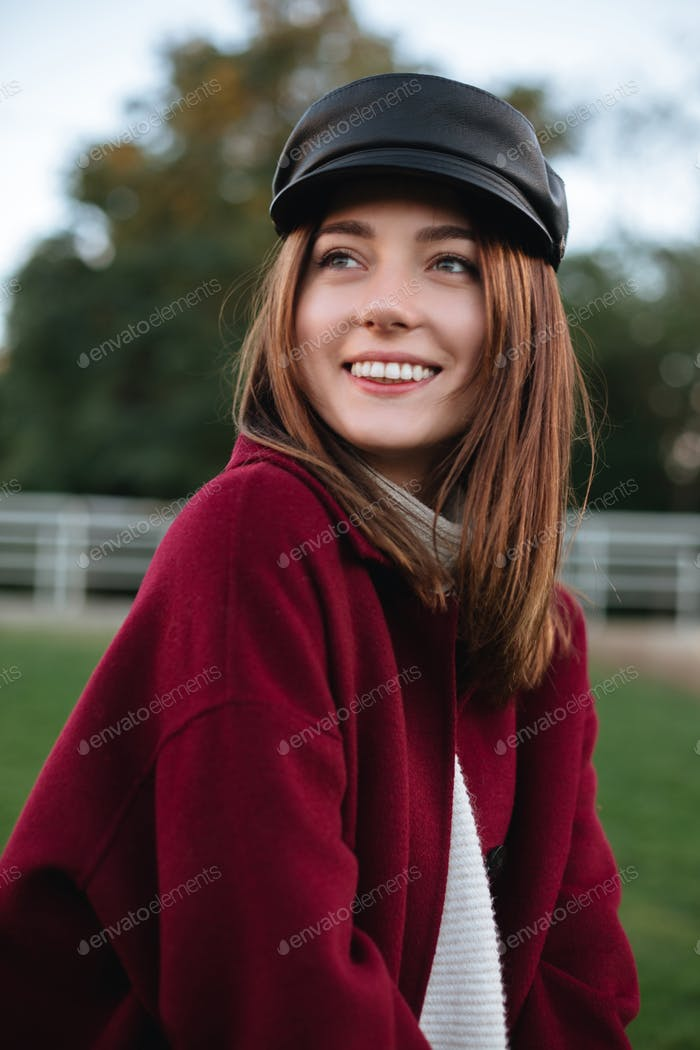 Beautiful lady in black cap and coat standing in park and happily looking aside