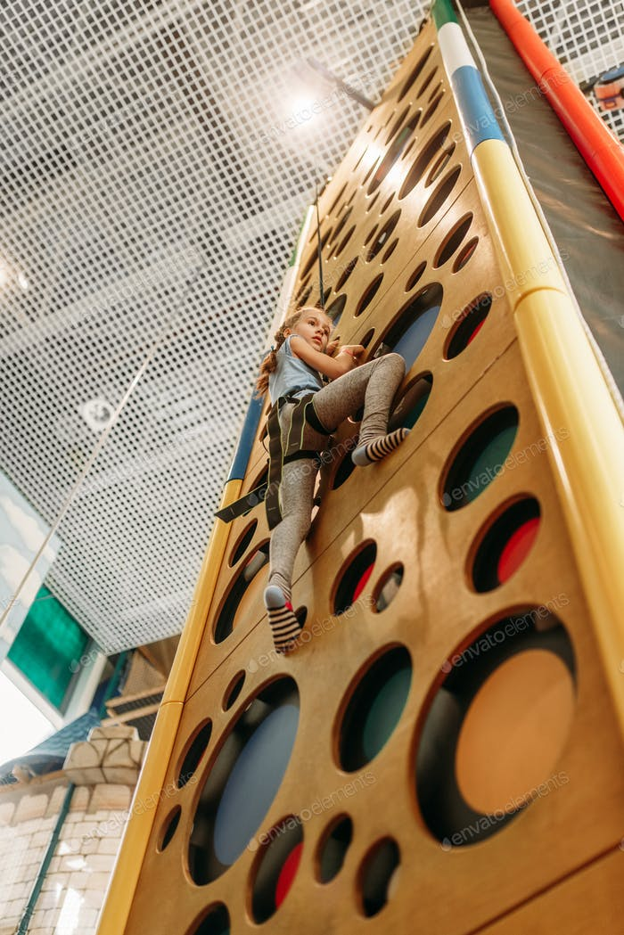 Girl climbing walls in game center, bottom view