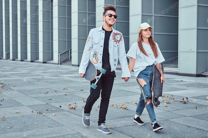 Attraktives trendiges gekleidetes Paar mit Skateboards im Freien