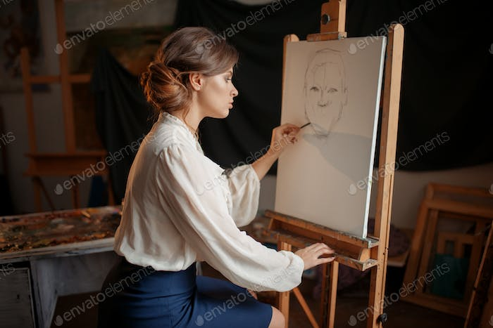 Female painter in studio, pencil sketch on easel
