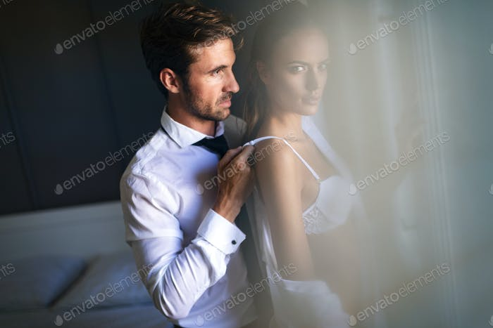 Portrait of sensual young lovers in bedroom