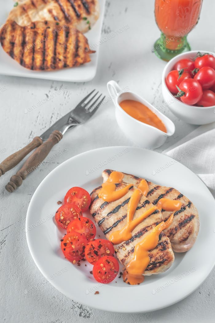 Grilled chicken breast with sauce and cherry tomatoes
