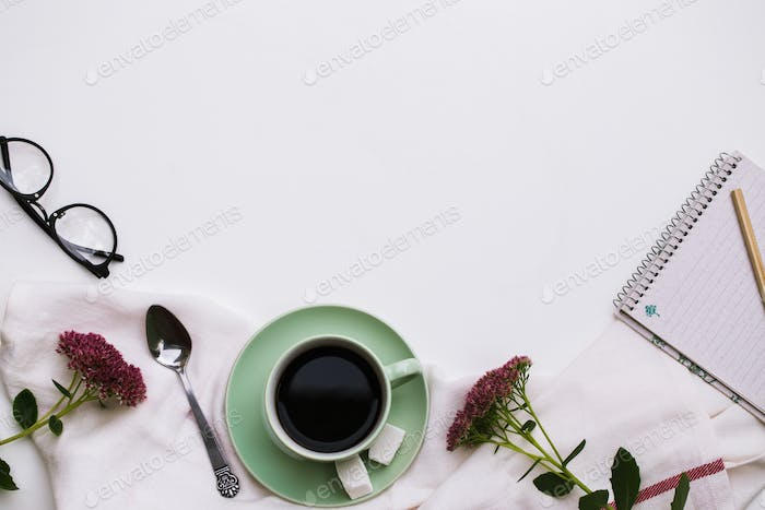 Notepad and cup of coffee on white background.