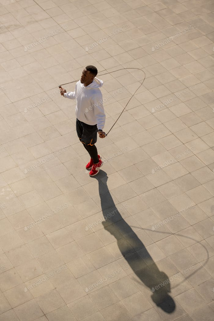 Young African sportsman in activewear jumping with skipping-rope outdoors