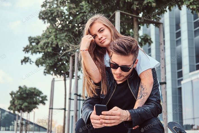 Attractive trendy dressed young couple sitting together on bench near a skyscraper.