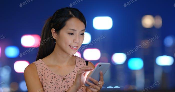 Frau Verwendung von Smartphone in der Nacht und stehend im Freien
