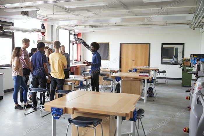 Group Of High School Students Standing Around Work Bench Listening To Teacher