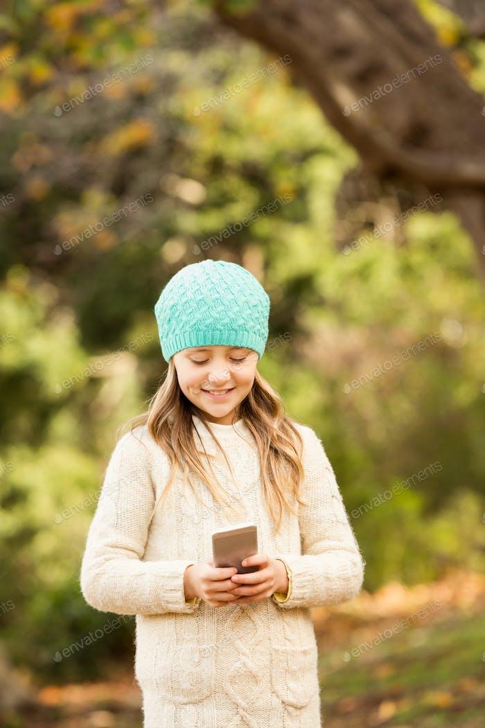 Glückliches kleines Mädchen im Park an einem Herbsttag