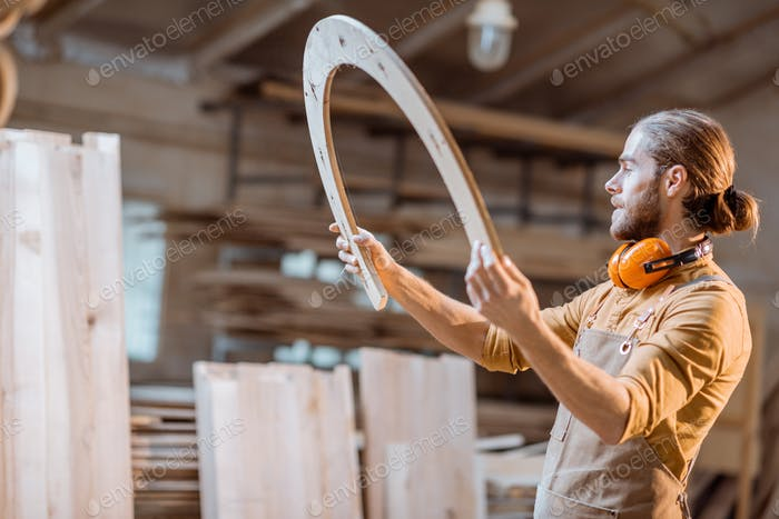 Carpenter with some wooden part at the workshop