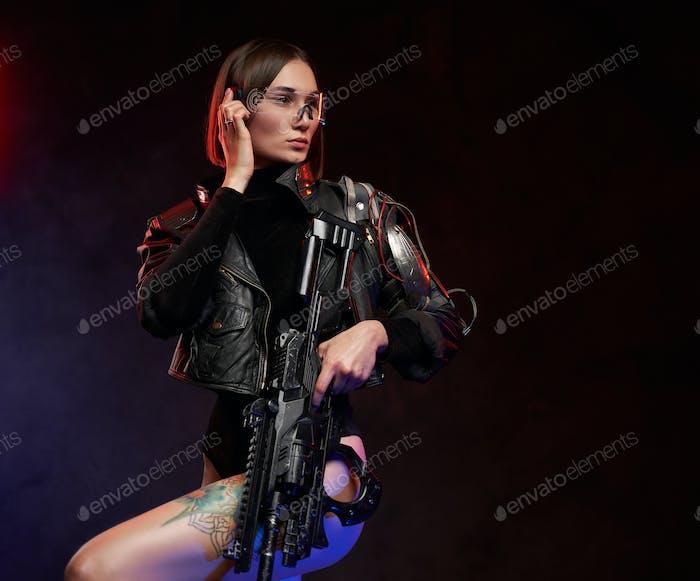 Martial woman communicates using her eyewear holding rifle in studio