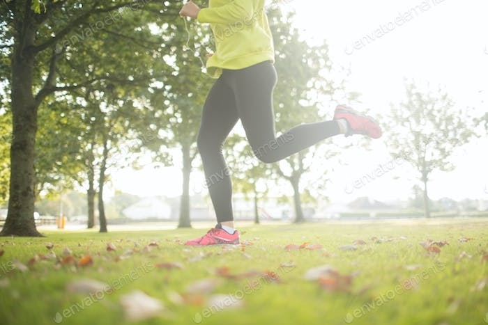 Active woman jogging in a park on a sunny day