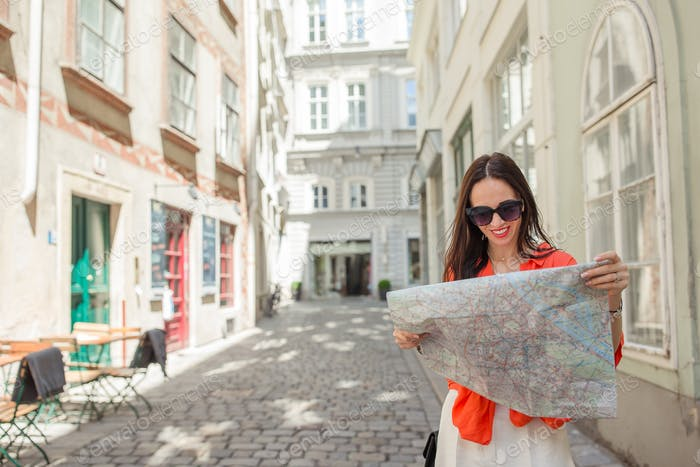 Young woman with a city map in city. Travel tourist girl with map in Vienna outdoors during holidays