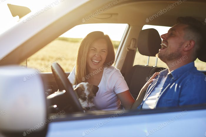 Joyful scene of young couple and dog during road trip