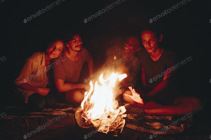 Group of young adult friends sitting around the bonfire outdoors recreational