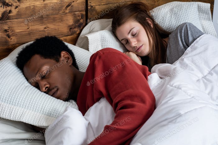 Young couple sleeping in a bed.