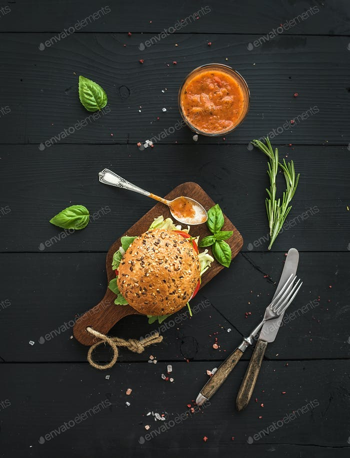 Fresh homemade burger on dark serving board with spicy tomato sauce