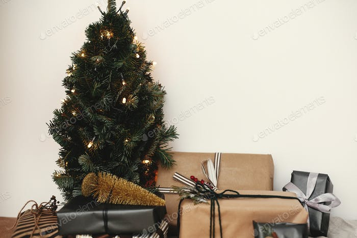 Stylish gift boxes under Christmas tree with festive golden lights in white room. Merry Christmas