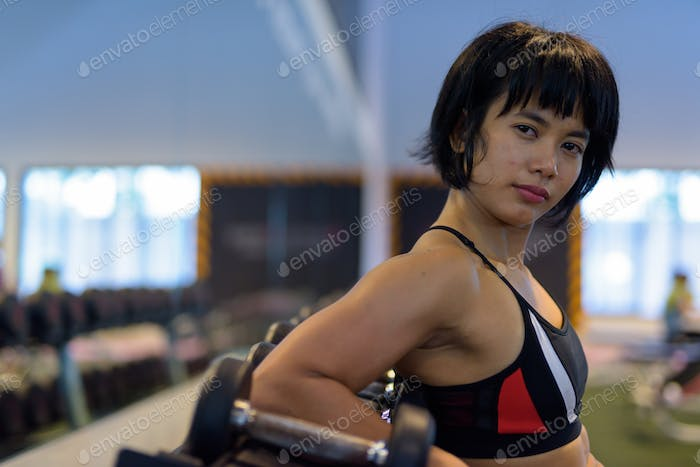 Portrait of young beautiful Asian woman at the gym